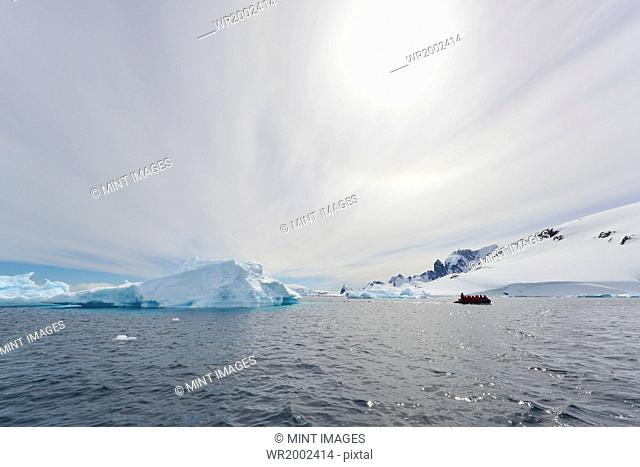 View of a group of people in a rubber boat near an iceberg offshore in the Antarctic