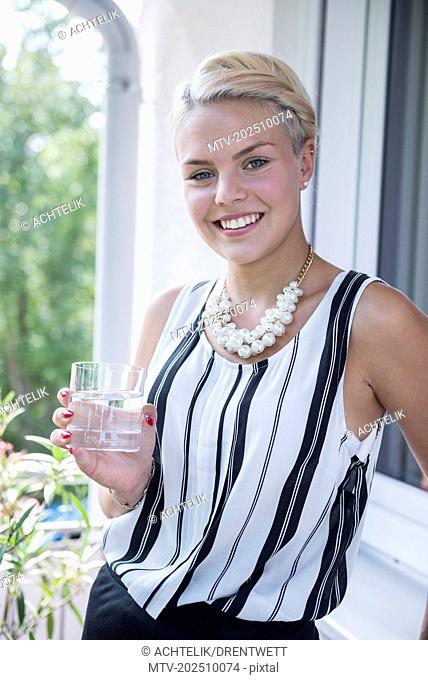 Portrait of a young woman drinking water on the balcony and smiling, Bavaria, Germany