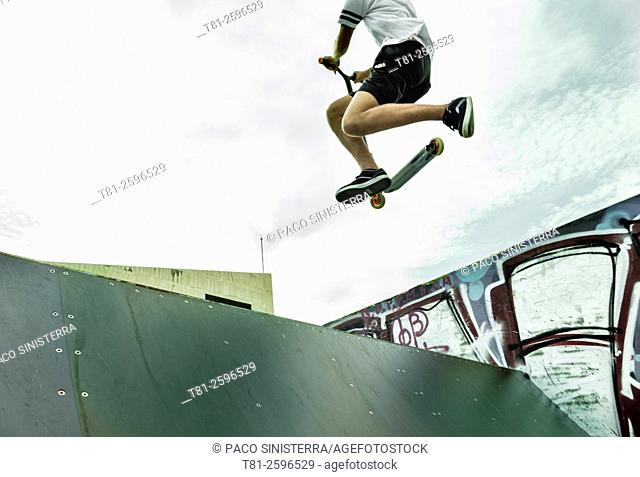 young man on escooter, jumping in skate park. Valencia. Spain