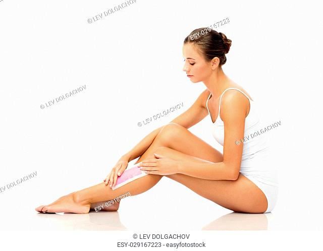 beauty, epilation, hair removal and people concept - beautiful woman applying depilatory wax strip to her leg skin over white background