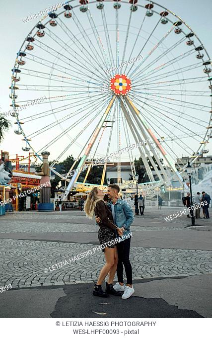Young couple in love, kissing and embracing at a funfair
