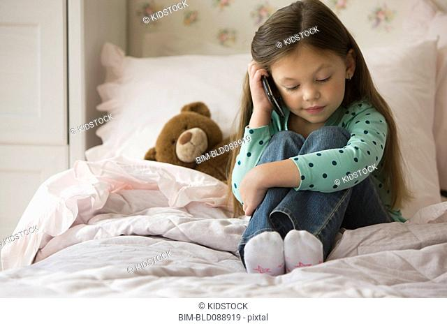 Caucasian girl sitting on bed talking on cell phone