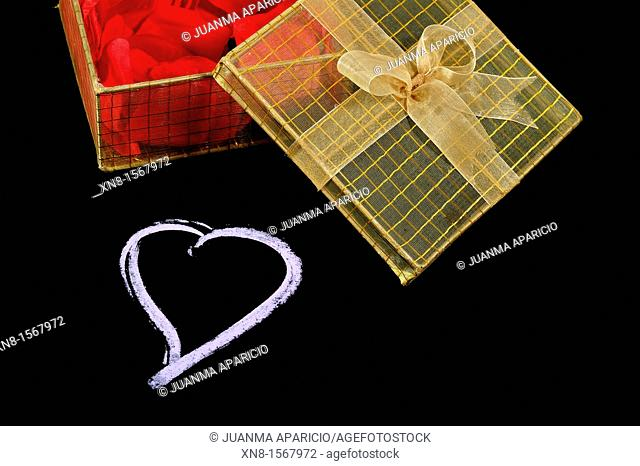 Heart drawn on black background with a gift box with a bow full of red petals