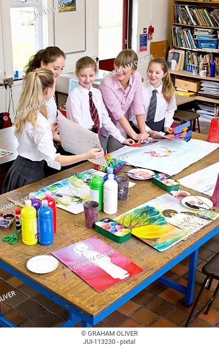 Art teacher painting with middle school students in art class