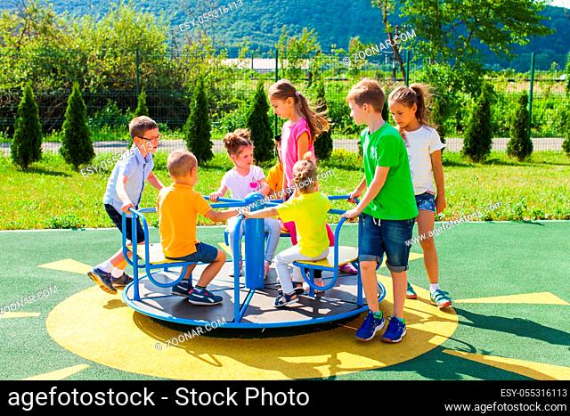 Cute boys and girls ride on a blue carousel on the playground