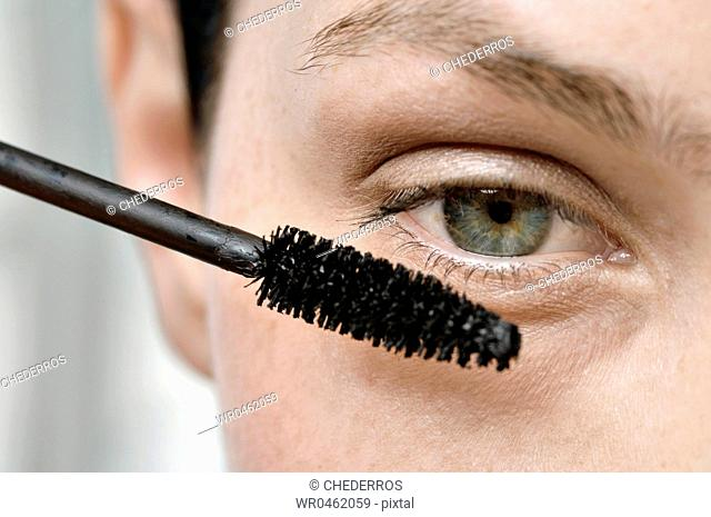 Close-up of a young woman applying mascara on her eyelashes