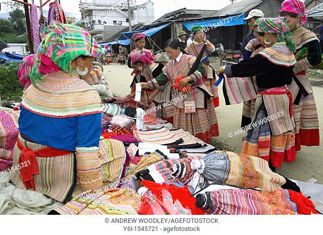 Young women inspect clothing and fabrics Bac Ha hilltribe market known for colourful Flower Hmong traders north Vietnam