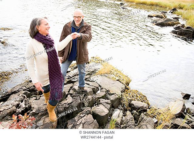 Mature couple walking over rocks