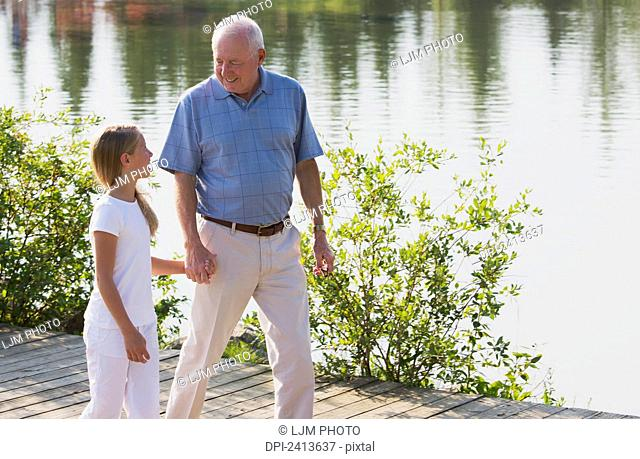 Grandfather and granddaughter spending quality time together in a park; Edmonton, Alberta, Canada