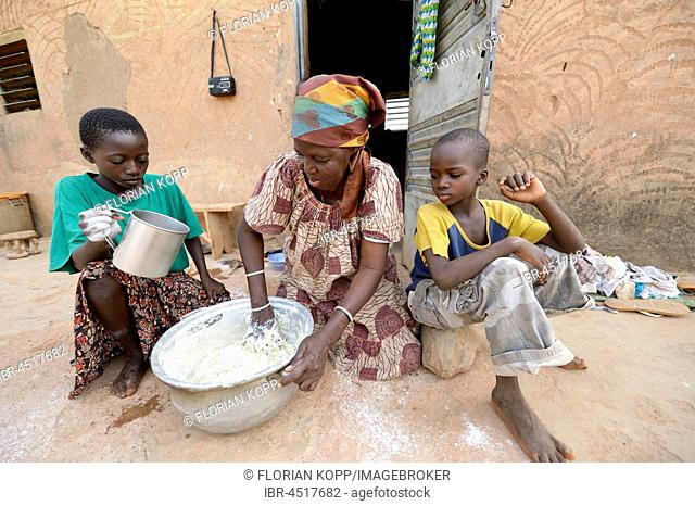 Woman and children kneading dough for flatbread, Toeghin village, Oubritenga province, Plateau Central region, Burkina Faso