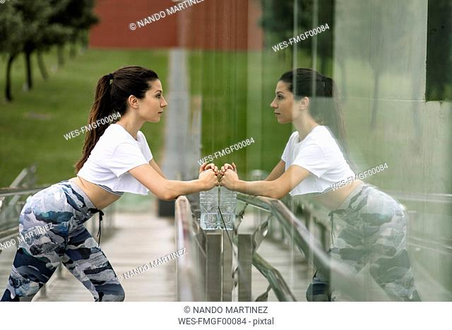 Young woman doing stretching exercise reflected in glass facade