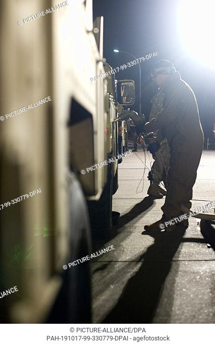 17 October 2019, Saxony-Anhalt, Burg: A soldier of the US army refuels the military vehicle of a US brigade from Fort Hood in Texas at an improvised gas station...