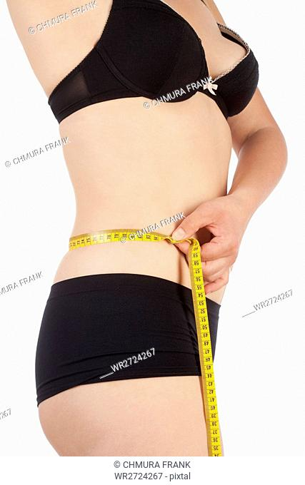 Woman in Black Underwear Measuring her Waist