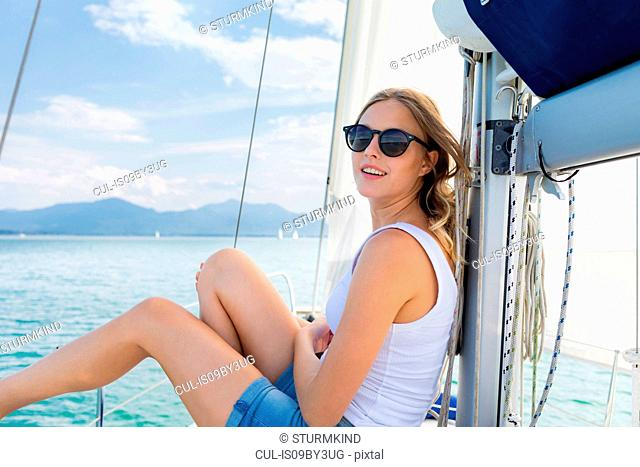 Young woman wearing sunglasses on sailboat on Chiemsee lake, portrait, Bavaria, Germany