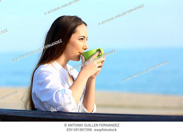 Side view portrait of a single happy woman drinking coffee and looking away on the beach