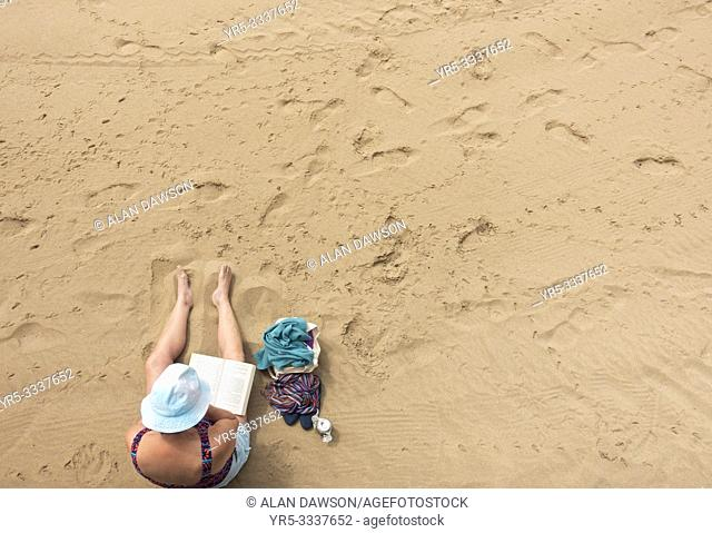 Elderly man reading book on Las Canteras beach in Las Palmas, Gran Canaria, Canary Islands, Spain