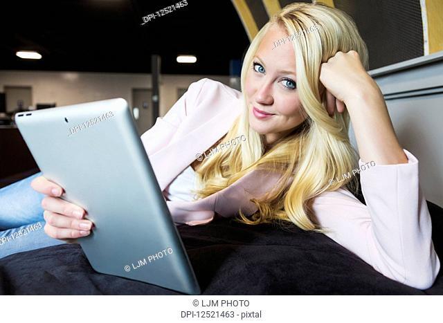 Business portrait of a beautiful young millennial businesswoman with long blond hair holding a tablet in a beanbag chair and posing for the camera in the...