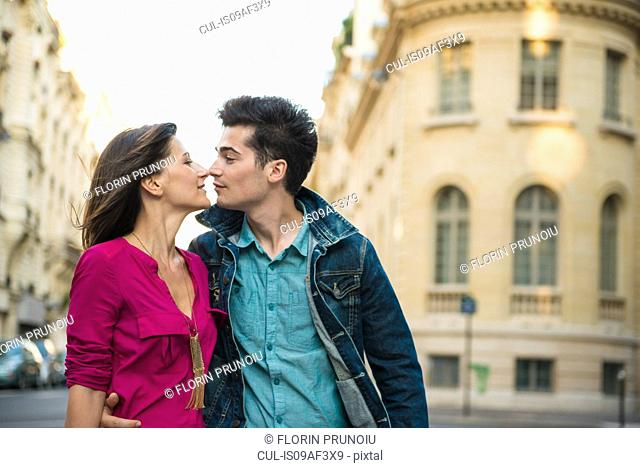 Young couple kissing on street, Paris, France