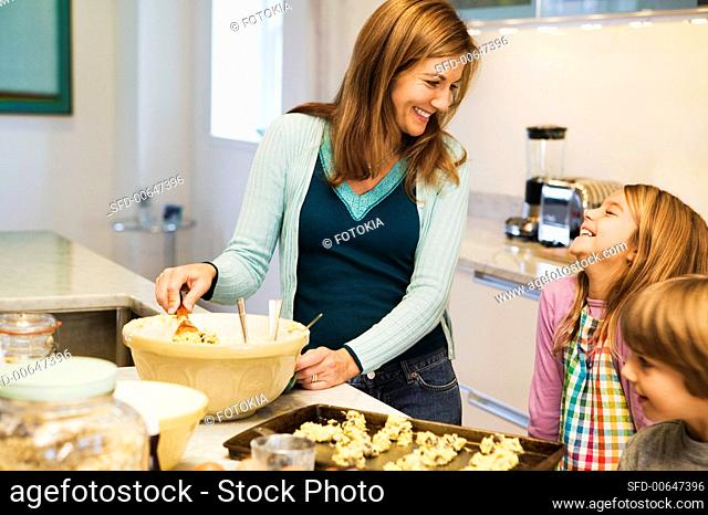 A Woman and Two Children Laughing and Making Cookies in the Kitchen