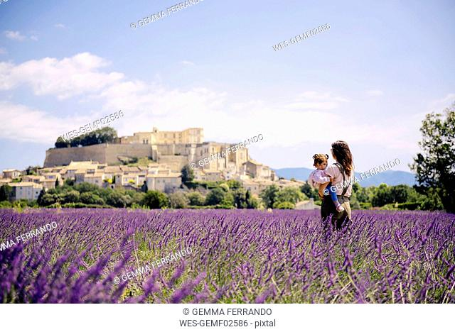 France, Grignan, mother standing in lavender field with little daughter on her arms looking at village