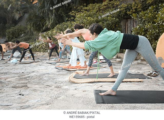Yoga group - multiple people exercising outdoors