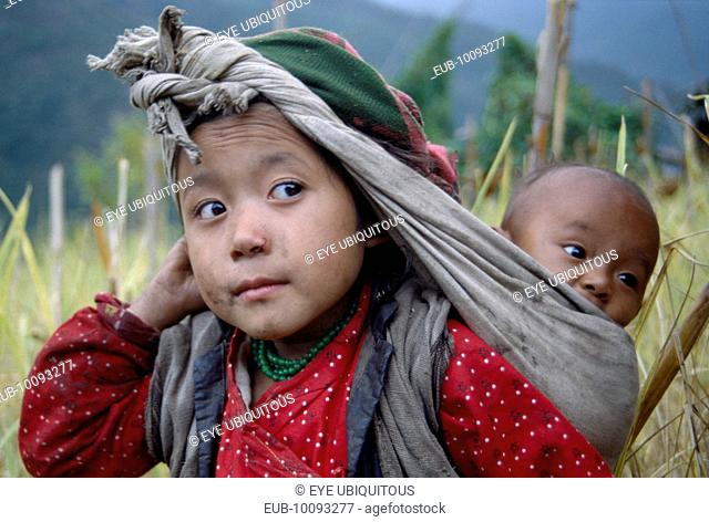 Rai girl carrying baby in sling on her back supported by cloth knotted around head