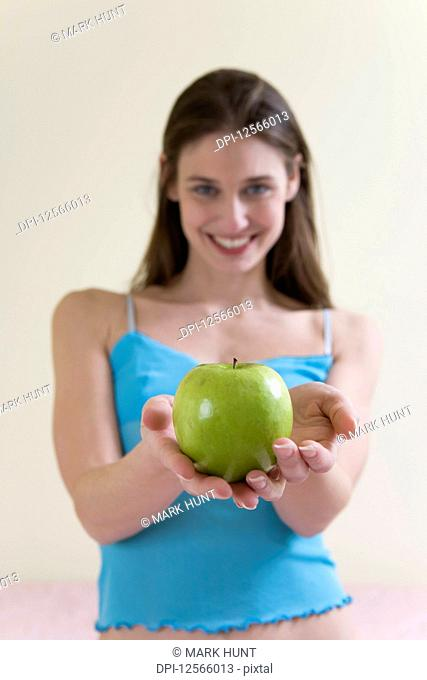 A beautiful young woman holding a green apple
