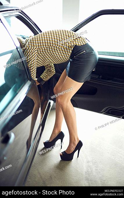 Young woman wearing mini skirt leaning into a car