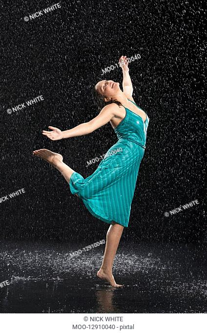 Woman standing on one leg leaning into falling rain