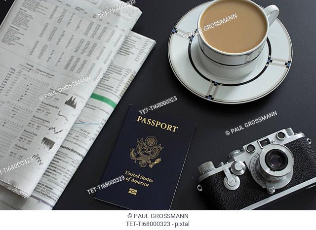 Passport, coffee, old camera and newspapers lying on table