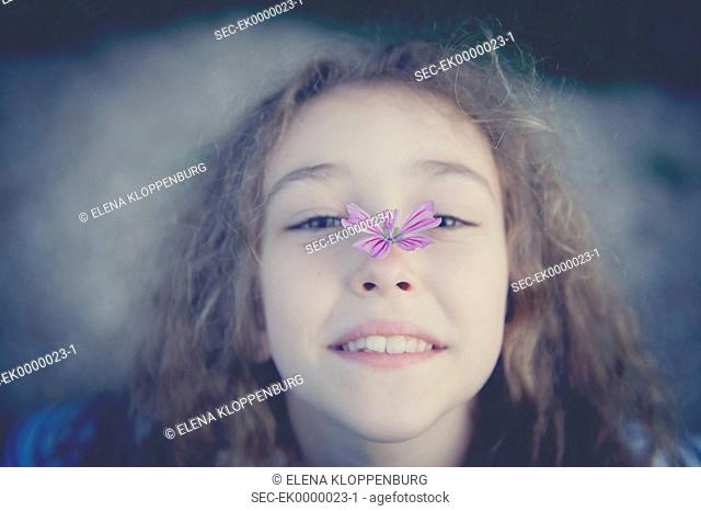 Italy, Smiling girl (10-12) with flower in shape of butterfly on her nose