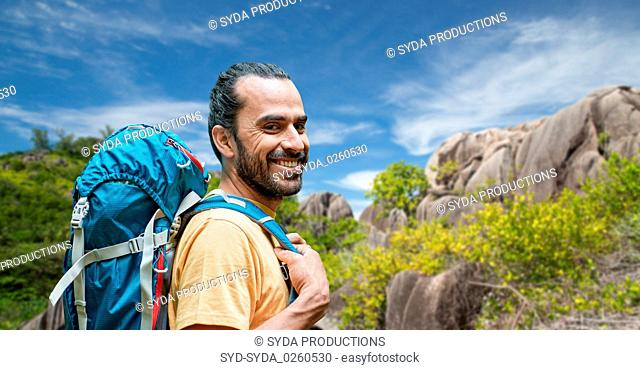 smiling man with backpack over seychelles