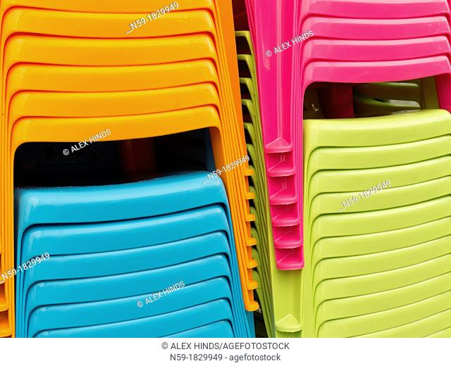 Colourful plastic chairs stacked on display in shop