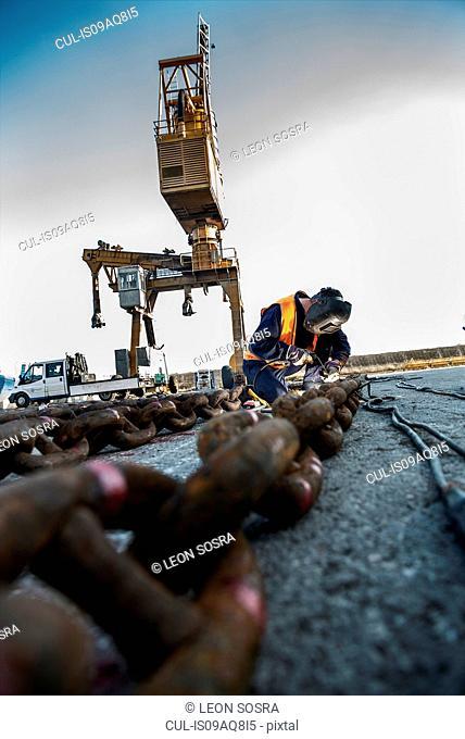 Welder welding chain on dock pier