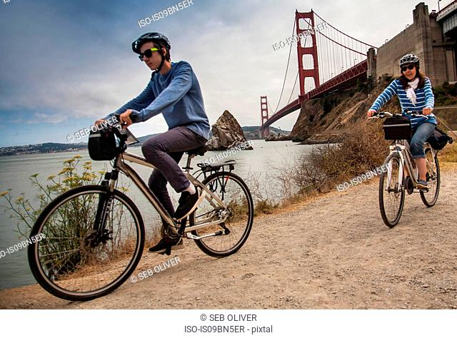 Tourists cycling, Golden Gate Bridge in background, San Francisco, USA