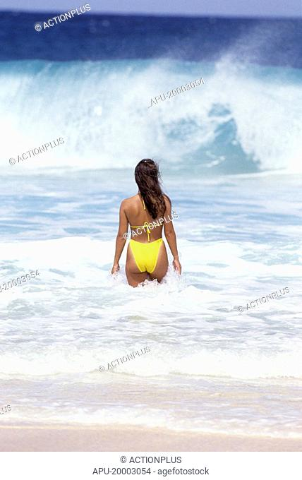 Woman in the sea watching the waves
