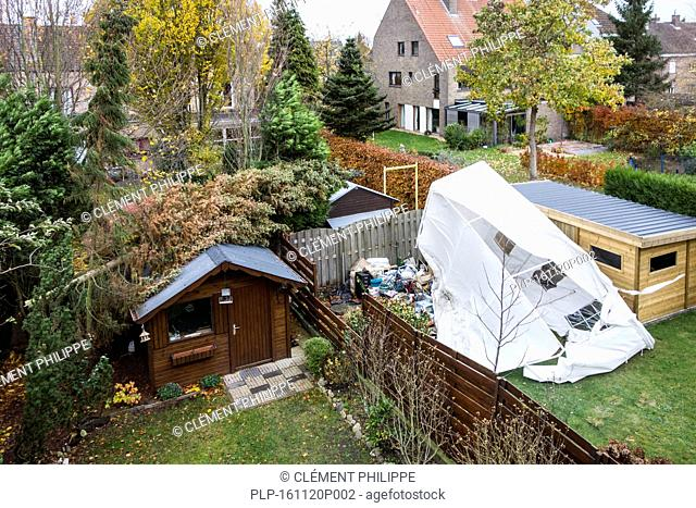 Broken tent and pine tree snapped in two and fallen on roof of garden house during autumn storm raging over Belgium