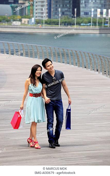 Young couple walking together holding hands and shopping bags