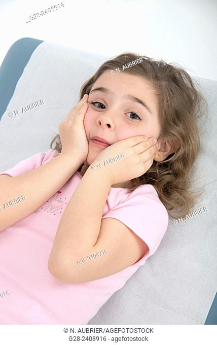 Little girl 7 lying on medical couch in surgery room and looking worried