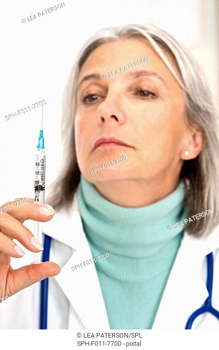 MODEL RELEASED. Mature female doctor holding an injection