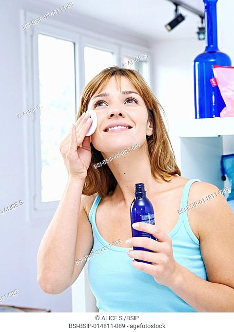 Woman applying floral water on her face