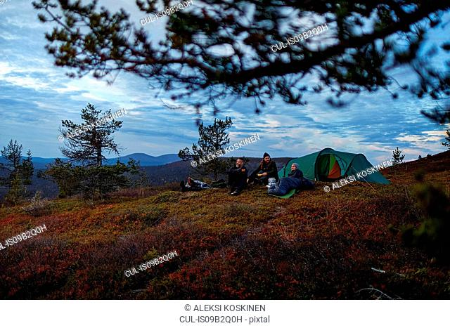Hikers relaxing in front of tent, Keimiotunturi, Lapland, Finland