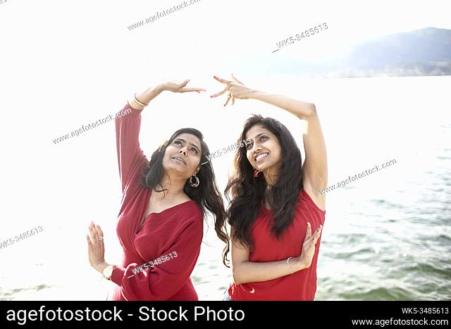 Two Indian women feeling connected with dancing traditional Indian dance, at lake Tegernsee, Bavaria, Germany