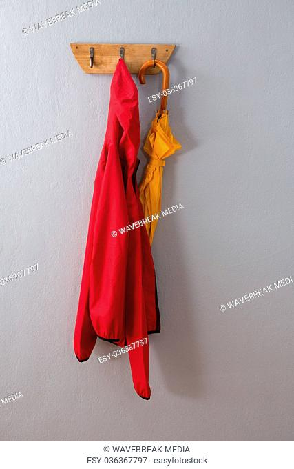 Red hoodie and umbrella hanging on hook