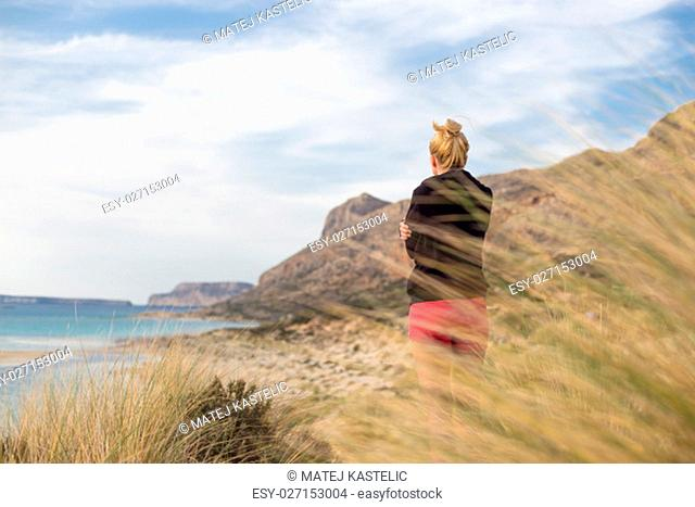 Woman, arms crossed, feeling chilled, enjoying last autumn sun, an beautiful Balos beach. Concept of vacations, freedom, happiness, enjoyment and well being