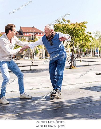 Adult grandson assisting senior man on skateboard
