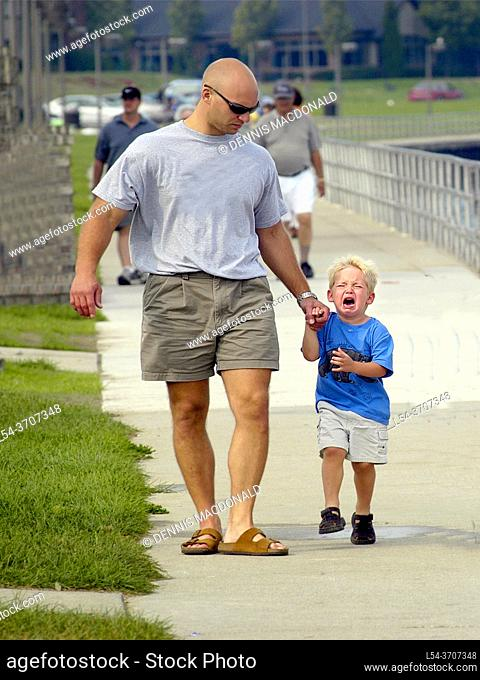 father walk with child toddler on a boardwalk one child is having temper tantrum angry outburst