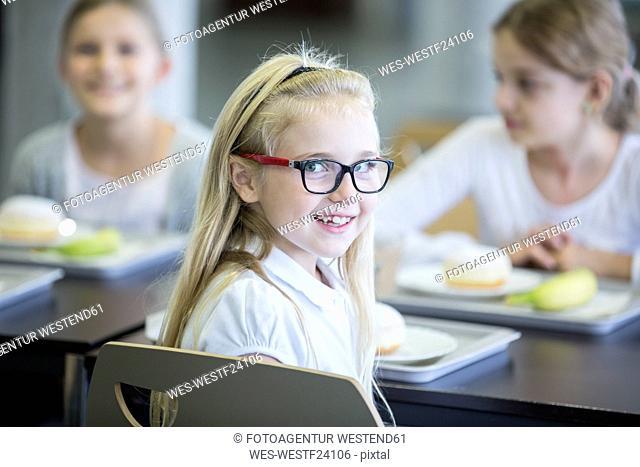 Portrait of smiling schoolgirl with classmates in school canteen