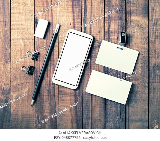 Smartphone and blank stationery on vintage wooden background. Responsive design template. Flat lay