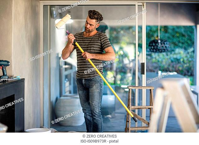 Man in unfurnished home, holding paint roller